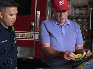 firefighter showing resident how to apply Yellow Dot sticker to car